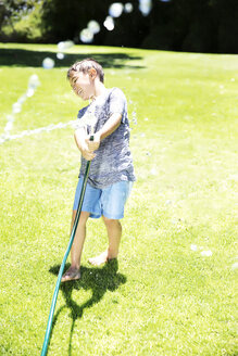 Boy splashing water with garden hose - TOYF000064
