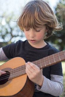 Little boy playing acoustic guitar - RAEF000149