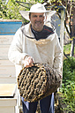 Bulgaria, Pleven, smiling beekeeper with honeycombs - DEGF000396
