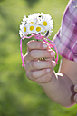 Little girl's hand holding bunch of daisys - YFF000410
