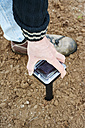 Gardener pushing a solar powered device against moles and voles into the ground - HAWF000773