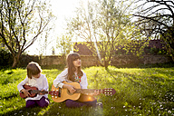Two sisters sitting on a meadow playing guitar - LVF003225