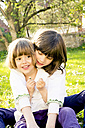 Two sisters sitting together on a meadow in the garden - LVF003233