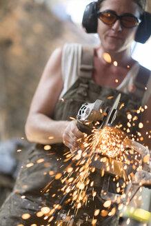 Female welder working in metal workshop - ABAF001669