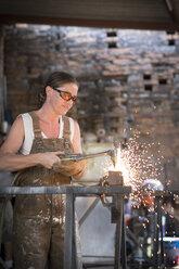 Female welder working in metal workshop - ABAF001674