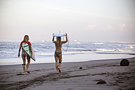 Indonesia, Bali, two women carrying surfboards on the beach - KNTF000003