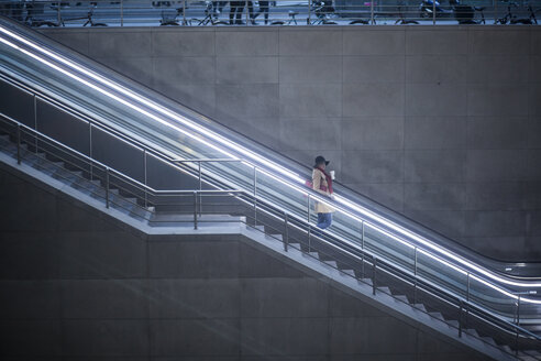 Young woman with coffee to go standing on escalator - MMFF000840