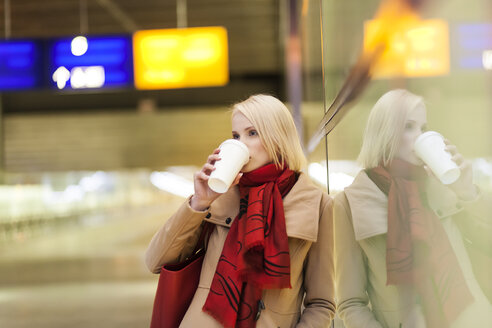 Young woman with coffee to go waiting in a station building - MMFF000848