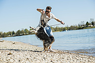 Germany, Mannheim, young man playing with dog at the riverside - UUF003929