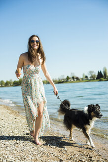 Germany, Mannheim, young woman walking with dog at River Rhine - UUF003934