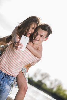 Playful young couple taking selfie outdoors - UUF003877