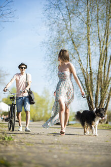 Young couple walking with dog outdoors in summer - UUF003879