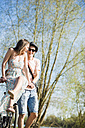 Playful young couple with bicycle - UUF003880