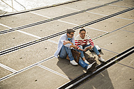 Young man and woman sitting on tracks using digital tablet - UUF003886