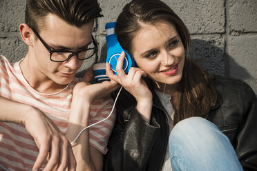 Smiling young couple sharing headphones - UUF003896