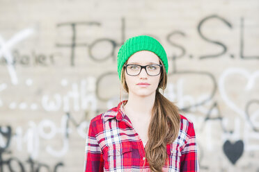 Young woman with checkered shirt and green wooly hat at graffiti wall - UUF003907