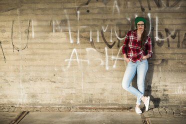 Young woman with checkered shirt and wooly hat leaning at graffiti wall - UUF003909