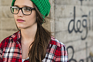Young woman with checkered shirt and green wooly hat at graffiti wall - UUF003910
