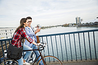 Germany, Mannheim, young man and woman with bicycle and cell phone on bridge - UUF003914