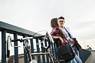 Young man and woman with bicycle on bridge - UUF003916