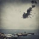 France, Biarritz, man standing on stone at seaside - DWI000474