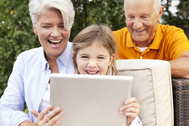 Happy grandparents and girl outdoors using digital tablet - MFRF000164