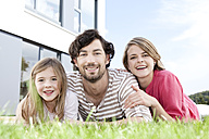 Portrait of happy family lying on lawn - MFRF000172