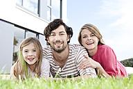 Portrait of happy family lying on lawn - MFRF000172