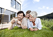 Happy grandmother, father and girl lying on lawn using cell phone - MFRF000175