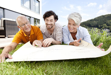 Adult son and parents lying on lawn looking at construction plan - MFRF000178