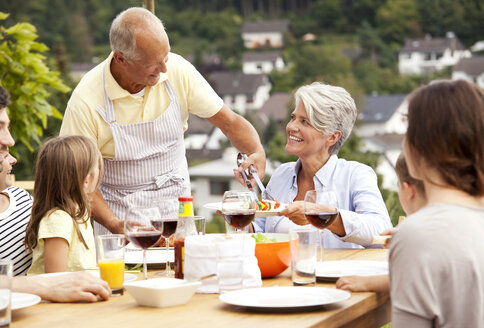 Grandfather serving food from barbecue grill for family at garden table - MFRF000204