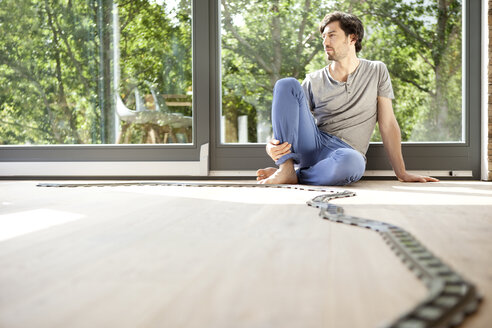 Pensive man sitting on floor with tracks of a toy train - MFRF000185