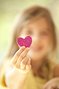 Close-up of girl holding glittering heart - MFRF000192