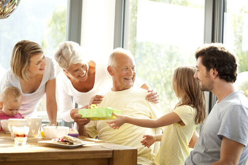 Senior man receiving present from his granddaughter at breakfast table - MFRF000210