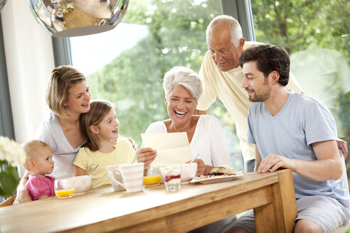 Happy granddaughter with her family reading letter at breakfast table - MFRF000213
