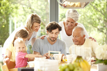 Father with his family reading postcard at breakfast table - MFRF000216