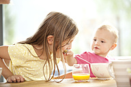 Baby girl feeding sister at breakfast table - MFRF000219