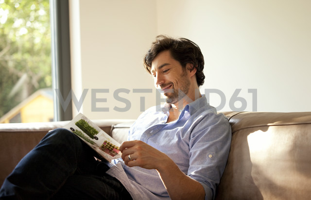 Man sitting on couch reading catalogue - MFRF000198 - Michelle Fraikin/Westend61