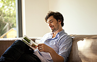 Man sitting on couch reading catalogue - MFRF000198