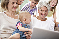 Extended family on couch using laptop - MFRF000225