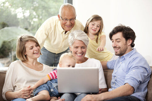 Extended family on couch using laptop - MFRF000228