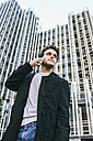 Spain, Madrid, young man on cell phone in front of a building - ABZF000010