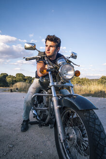 Spain, Madrid, young man leaning on his motorbike on a dirt road at sunse - ABZF000026