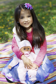 Little girl outdoors playing with a doll - GDF000711