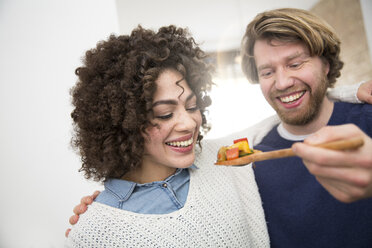 Couple cooking in kitchen tasting food - FKF000955