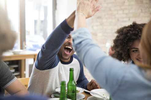 Happy friends at dining table with beer bottles high fiving - FKF000964