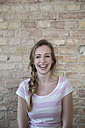 Portrait of laughing young woman in front of brick wall - FKF000976