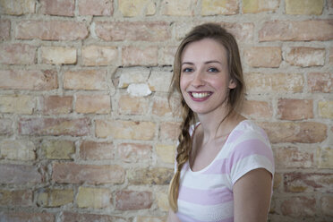 Portrait of smiling young woman in front of brick wall - FKF000977