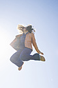 Young woman jumping in the air at backlight - ABZF000022