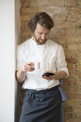 Cook with espresso cup and smartphone having a rest - FKF001044